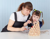 Mother and daughter building tower of bingo — Stock Photo