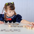 Little girl playing with lotto sitting — Stock Photo