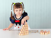 Little girl builds tower of lotto — Stock Photo