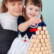 Stock Photo: Mom and daughter play - to build a tower