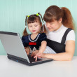 Mom shows daughter work on computer — Stock Photo