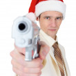 Guy in Christmas hat aiming a gun — Stock Photo
