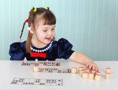 Child playing with bingo at the table — Stock Photo