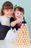 Mom and daughter play - to build a tower — Stock Photo