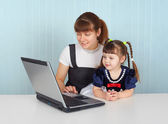 Woman and child sitting with laptop — Stock Photo