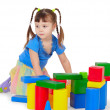 Little girl is playing with color bricks - Stock Photo