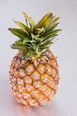 Pineapple on a grey surface — Stock Photo
