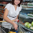 Happy young woman in supermarket — Stock Photo