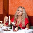 The beautiful girl in red at restaurant — Stock Photo