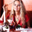Stock Photo: The beautiful girl in red at restaurant