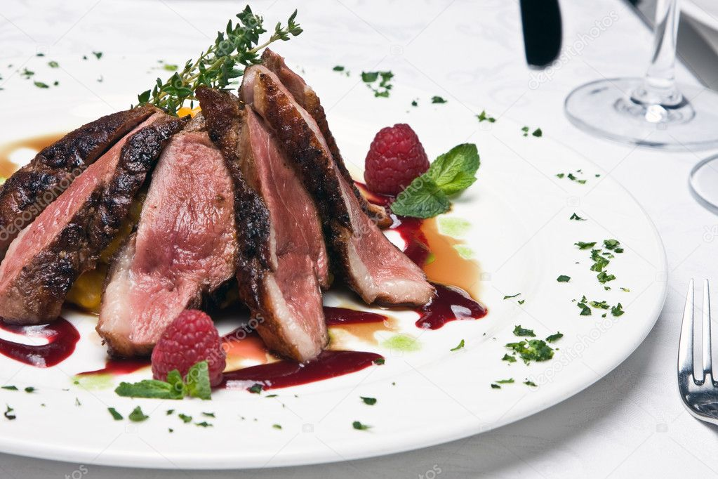 Slices of the beef meat on a dish decorated by sauce and berries — Stock Photo #1056027