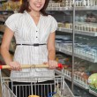 Beautiful young woman in supermarket — Stock Photo