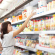Woman in the supermarket choose food - Stock Photo