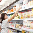 Woman in the supermarket choose food - Stockfoto