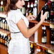 Stock Photo: Young girl chooses wine in supermarket