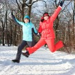 Two cheerful friendly girls jump in park - Stock Photo