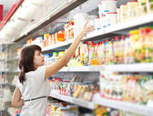 Woman in the supermarket choose food — Stok fotoğraf