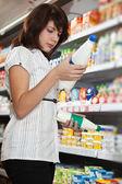 La chica del comprador en tienda elige leche — Foto de Stock