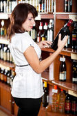Young girl chooses wine in a supermarket — Stock Photo