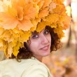 Girl in a wreath from autumn leaves — Stock Photo