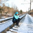 Woman sitting on rails of the railway - Stok fotoraf