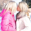 Two blonde girlfriends kiss in park — Stock Photo #1085517