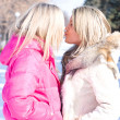 Two blonde girlfriends kiss in the park — Stock Photo
