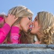 Two girlfriends blondes kiss on blue sky — Stock Photo