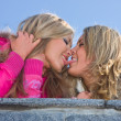 Stock Photo: Two girlfriends blondes kiss on blue sky