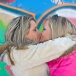 Two blonde girlfriends embrace and kiss — Stock Photo