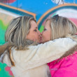 Stock Photo: Two blonde girlfriends embrace and kiss