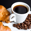 Stock Photo: White cup coffee and croissant on black