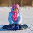 Girl on skates sitting on the ice. - Stock Photo