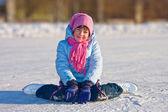 Girl on skates sitting on the ice. — Stock Photo