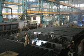Welders welding a metal part in a dark industrial environment. — Stock Photo