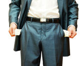 Businessman with empty pockets on white — Stock Photo