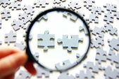 Magnifying glass and puzzle — Stok fotoğraf