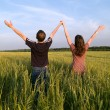 Young Couple Walking Field Holding Hands - Stock Photo