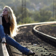 Young woman sitting on rail — Stok fotoğraf