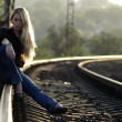 Young woman sitting on rail — Stock Photo