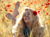 Barefoot blonde in poppies — Stock Photo