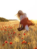 Blonde walking in poppy field — Stock Photo
