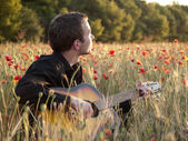 Guitarist in field — Stock Photo
