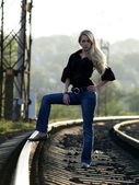 Young woman staying on railway — Stock Photo