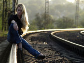 Young woman sitting on rail — Photo