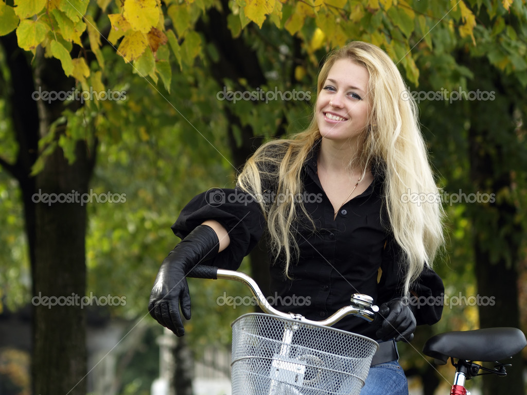 Young beautiful blond woman on bicycle under maple tree. Fall — Stok fotoğraf #1075988