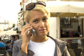 Blond woman talking by telephone — Stock Photo