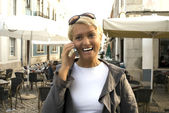 Blond woman talking by phone — Stock Photo