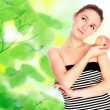 Young woman with apple over green — Stock Photo