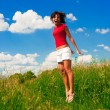 Stock Photo: Happy young womjumping in field